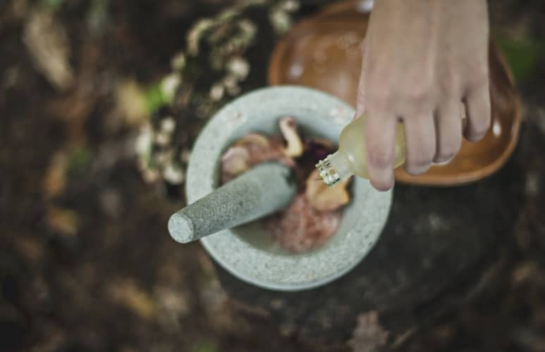 person pouring liquid from bottle inside mortar and pestle