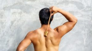 man scratching his back with wooden backscratcher