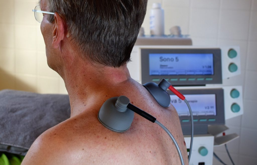 Man being treated with professional TENS unit for back pain