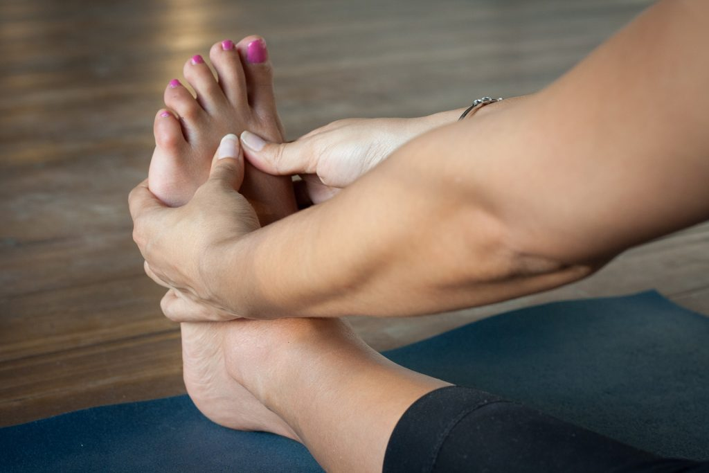 A waoman uses foot zoning massage on her own foot