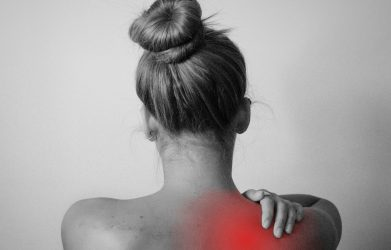 A woman's back with red over her right shoulder to indicate that she needs to learn how to use a tens unit for shoulder pain